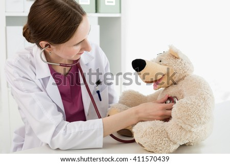 Family doctor examination. Beautiful smiling female doctor in white coat examine teddy bear with stethoscope to calm down and interest child. Playing with baby patient. Pediatrics medical concept. - stock photo
