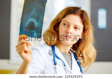 Family doctor examining x-ray picture. - stock photo