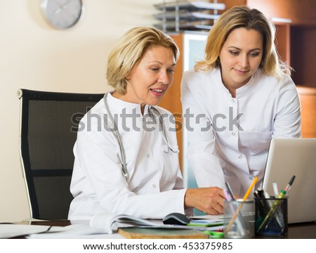 Family doctors therapeutists working at PC in modern office