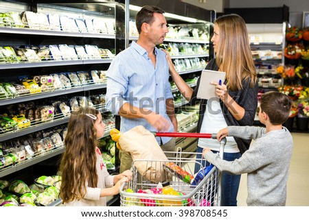 Family doing grocery shopping at the supermarket - stock photo