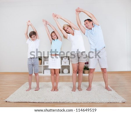 Family Doing Stretching Exercises On The Carpet At Home