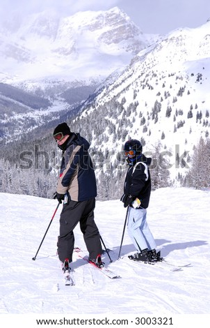 Family downhill ski vacation in snowy Canadian Rockies - stock photo
