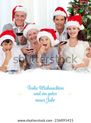 Family drinking wine and eating sweets in Christmas against border - stock photo