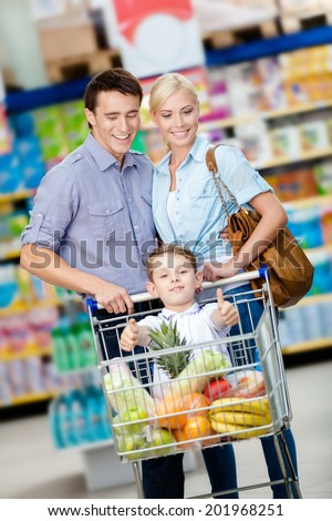 Family drives cart with food and boy sitting there. Concept of fresh and healthy food and consumerism - stock photo