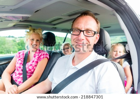 Family driving in car with seat belt fastened - stock photo