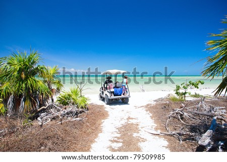 Family driving in golf cart along the tropical beach - stock photo