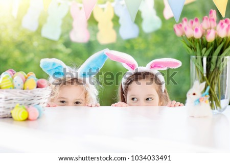 Family Easter morning. Children dye eggs. Kids with bunny ears search for candy and chocolate eggs on Easter egg hunt. Home decoration with tulip flowers, pastel rabbit banner and dye egg basket.