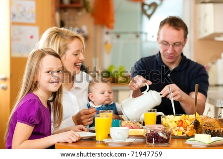 Family eating breakfast in the kitchen of their house - stock photo