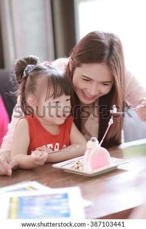 Family eating cake in restaurant - stock photo