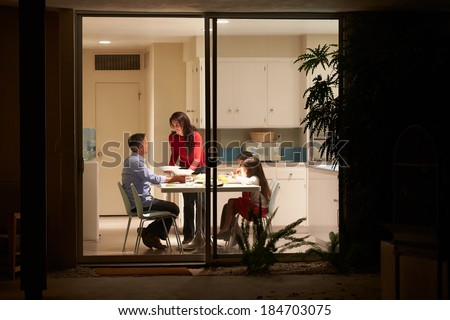 Family Eating Evening Meal Viewed From Outside - stock photo