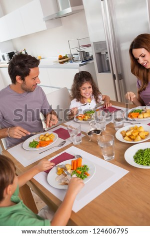 Family eating healthy dinner in kitchen - stock photo