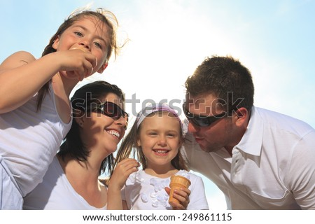 family eating ici cream in front of ocean - stock photo