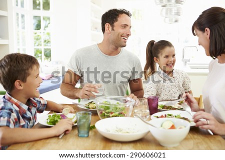 Family Eating Meal Around Kitchen Table Together - stock photo