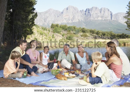 Family Eating Picnic by Lake - stock photo