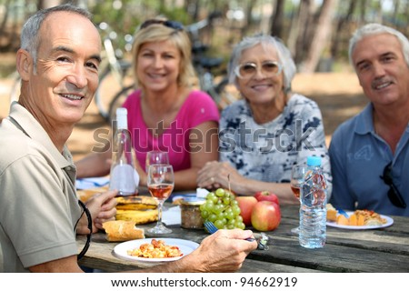 family eating picnic in the forest - stock photo