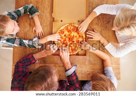 Family eating pizza together, overhead view - stock photo
