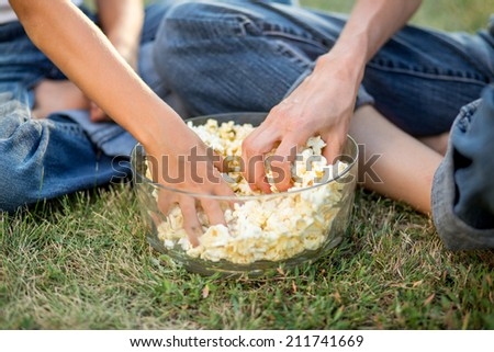 Family eating pop corn while sitting on green grass - stock photo