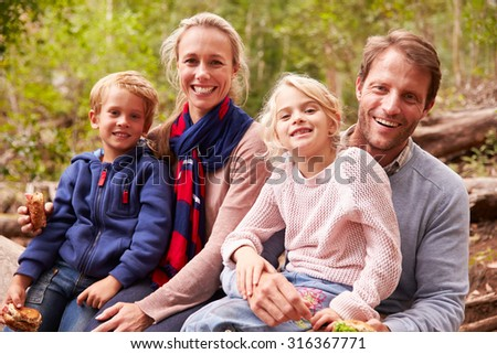 Family eating sandwiches outdoors in a forest, portrait - stock photo
