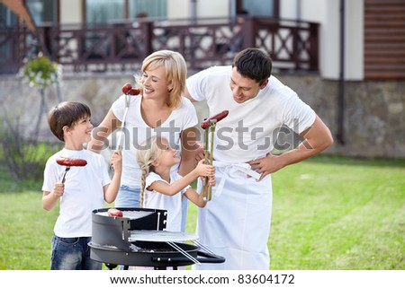 Family eating sausages in the open air - stock photo
