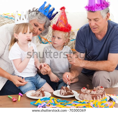 Family eating the birthday cake together at home