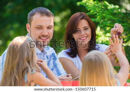 Family eating together outdoors at park on backyard - stock photo