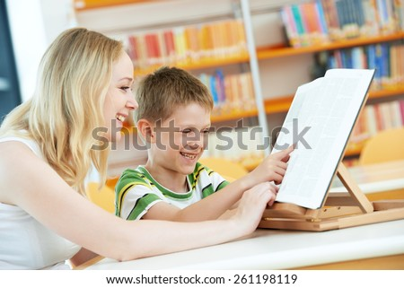 Family education. Mother woman and child boy in library reading books - stock photo