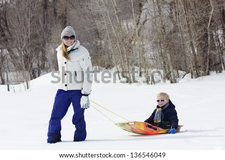 Family enjoying a day Snow sledding - stock photo