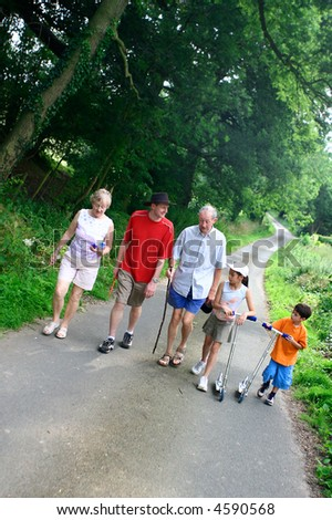 Family enjoying a walk in the countryside. Grandparents, parent, a daughter and a son. - stock photo