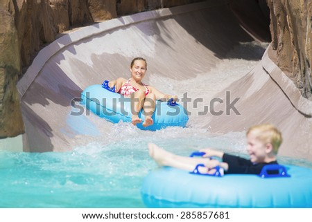 Family enjoying a wet ride down a water slide - stock photo