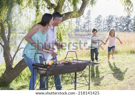 Family Enjoying Barbeque By Lake - stock photo
