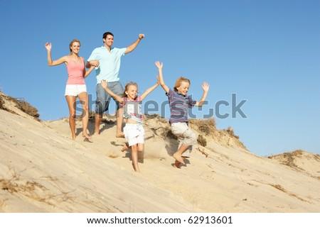 Family Enjoying Beach Holiday Running Down Dune - stock photo