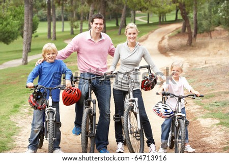 Family enjoying bike ride in park - stock photo