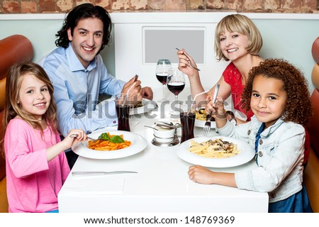 Family enjoying dinner outdoors on weekend - stock photo