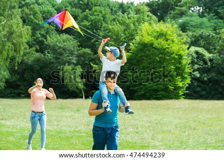 Family Enjoying In The Park While Flying The Colorful Kite