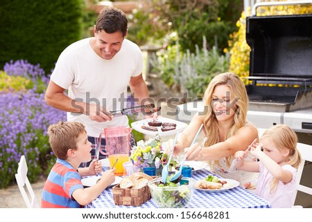Family Enjoying Outdoor Barbeque In Garden - stock photo