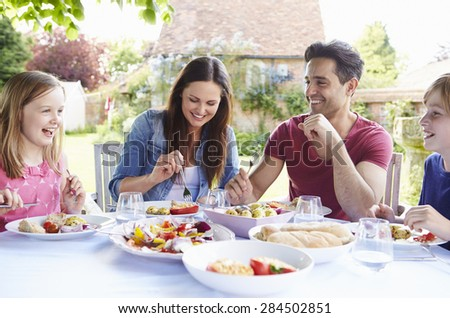 Family Enjoying Outdoor Meal Together - stock photo