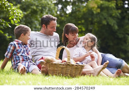 Family Enjoying Summer Picnic In Countryside - stock photo