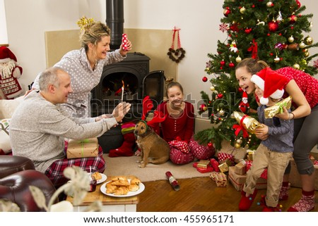 Family enjoying their Christmas morning. The father is using a smartphone to take a photo of two of his children. The mother and one of the sisters are watching.  - stock photo