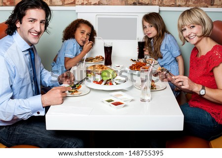 Family enjoying their dinner at a restaurant - stock photo