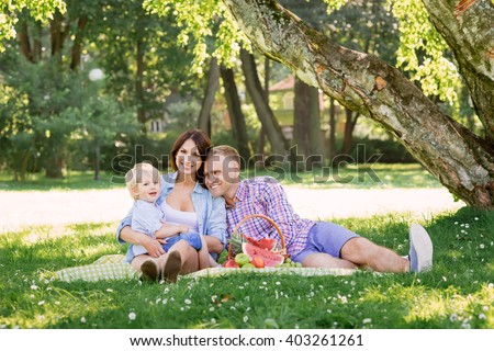 Family enjoying their leisure having a picnic in the park. - stock photo