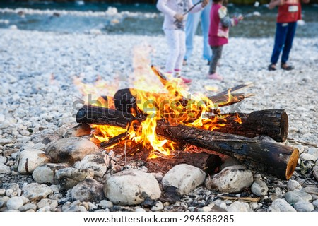 Family enjoying time by the river and self-made campfire during adventurous camping trip, spending quality time together.  Active natural lifestyle, family time concept.  - stock photo