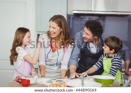 Family enjoying while cooking food in kitchen at home - stock photo