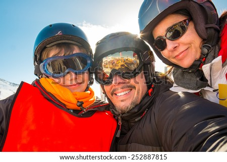 Family enjoying winter vacations and waving to a camera taking selfie photograph. Skiing, winter, snow, skiers, sun and fun