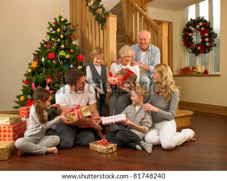 Family exchanging gifts in front of Christmas tree - stock photo