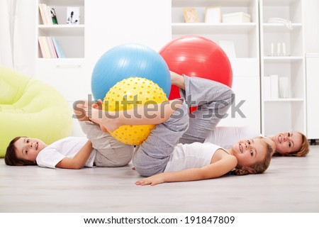 Family exercising with large gymnastic balls - laying on the floor at home - stock photo