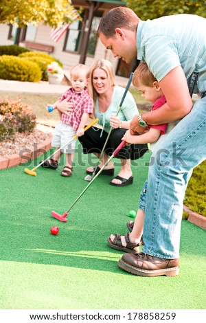 Family: Family Time Playing Mini-Golf In The Summer - stock photo