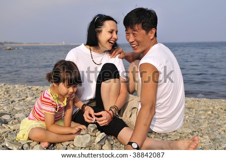 Family, fanny  playing outdoor on the beach near the water