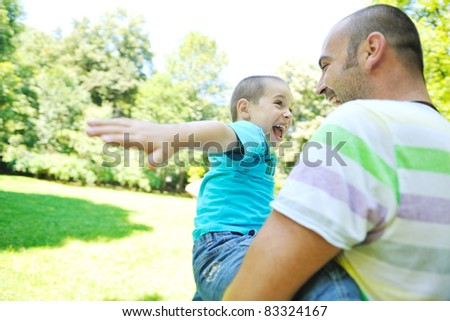 family father and son have fun at park on summer season and representing happines concept - stock photo