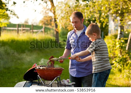 Family - father and son - having a barbecue party, the child is turning meat and sausages, both having fun - stock photo
