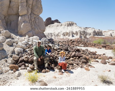 Family (father and two children) sitting on the rocks, resting. Big Bend National Park, Texas, United States - stock photo
